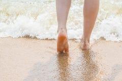 Ноги женщины идя на песок пляжа Стоковые Изображения