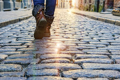 Ноги женщины идя вдоль мощенных булыжником городов европейца улиц Стоковая Фотография