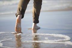 Ноги женщины идя морским путем берег Стоковое фото RF