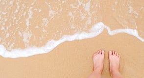 Ноги женщины на песчаном пляже стоковая фотография