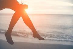 Ноги женщины на пляже на деревянном качании с заходом солнца Незамужняя женщина co стоковые изображения rf