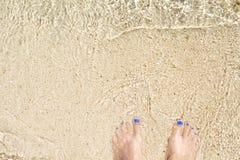 Ноги женщины на пляже с белым песком Тропический seashore острова Предпосылка фото взгляд сверху пляжа Стоковые Фотографии RF