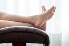 Ноги женщины на стуле Стоковые Изображения