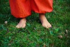 Ноги женщины на траве с оранжевыми брюками Стоковые Фото