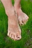 Ноги женщины на траве. Стоковые Фото