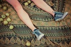 Ноги женщины окруженной яблоками Стоковые Изображения