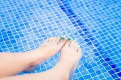 Ноги женщины ослабляя в бассейне Стоковое Изображение