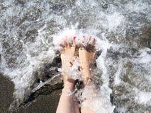 Ноги женщины ослабляя на волне берега ждать Стоковое Изображение