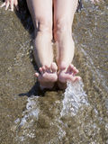 Ноги женщины ослабляя на волне берега ждать Стоковое Фото