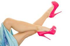 Ноги женщины поднимают и пересекли в голубую юбку и розовые пятки стоковые фото