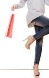 Ноги женщины при красные изолированные хозяйственные сумки Стоковая Фотография