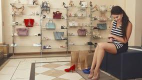 Ноги женщины пробуя бежевые ботинки дальше сток-видео
