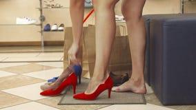 Ноги женщины пробуя красные ботинки на конце вверх акции видеоматериалы