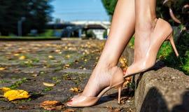 Ноги женщины сидя на скамейке в парке Стоковое фото RF