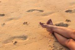 Ноги женщины сидят на пляже Стоковое Изображение RF