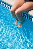 Ноги женщины сидя на бассейне обочины Стоковое Изображение RF