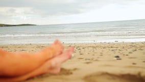 Ноги женщины сидя на пляже водой акции видеоматериалы