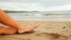 Ноги женщины сидя на пляже сток-видео