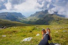 Ноги женщины сидя на траве в горах Стоковое Фото