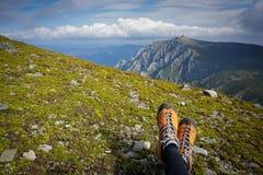Ноги женщины сидя на траве в горах Стоковые Изображения