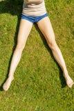 Ноги женщины сидя на траве Стоковые Фото