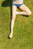 Ноги женщины сидя на траве Стоковые Изображения