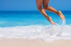 Ноги женщины, скача на пляж Стоковая Фотография