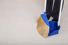 Ноги женщины с полом веника и dustpan широким Стоковая Фотография