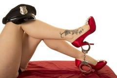 Ноги женщины с татуировкой и красные ботинки ловят шляпу и тумаки Стоковые Фото