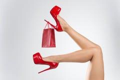 Ноги женщины с хозяйственными сумками на белой предпосылке Стоковые Фотографии RF