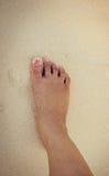 ноги женщин в песке моря Стоковая Фотография