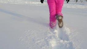 Ноги женщин крупного плана идут через глубокий сугроб в зиме в поле сток-видео