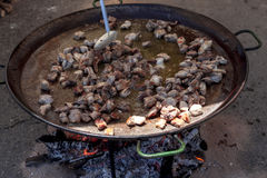 ноги зажаренные цыпленком Подготовка паэлья цыпленка национальное испанское блюдо паэлья в большом skillet сварено на открытом ог стоковые фото