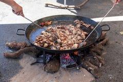 ноги зажаренные цыпленком Подготовка паэлья цыпленка национальное испанское блюдо паэлья в большом skillet сварено на открытом ог стоковая фотография