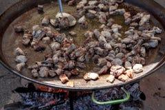 ноги зажаренные цыпленком Подготовка паэлья цыпленка национальное испанское блюдо паэлья в большом skillet сварено на открытом ог стоковая фотография rf