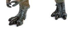 Ноги игрушки тиранозавра на белизне Стоковое Изображение