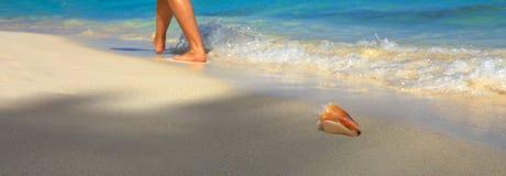 Ноги и ноги женщины идя на карибский пляж Стоковые Изображения
