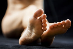 Ноги и ноги женщины с темной предпосылкой Стоковые Изображения