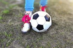 Ноги и шарик Girl's на траве весны зеленой стоковые фотографии rf