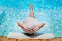 Ноги и шляпа женщины в бассейне мочат стоковые изображения rf