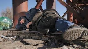 Ноги конца-вверх бездомного человека спать outdoors видеоматериал