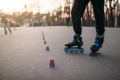 Ноги конькобежца ролика в коньках на дорожке асфальта Стоковые Фото