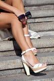 Ноги красивейшей девушки в сидеть высоких пяток Стоковые Изображения RF