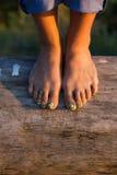 Ноги красивой девушки на дереве с pedicure Стоковое фото RF