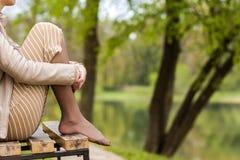 Ноги красивой молодой женщины сидя на стенде в парке Стоковые Изображения