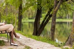 Ноги красивой молодой женщины сидя на стенде в парке Стоковое Фото