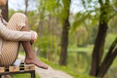 Ноги красивой молодой женщины сидя на стенде в парке Стоковое фото RF