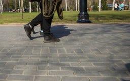 Ноги людей идя в ботинки спорт вниз по улице на солнечный день стоковые фотографии rf