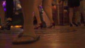 Ноги людей танцуя на танцплощадке на партии в ночном клубе Танцоры танцуя и имея потеха на танцевальном зале на дискотеке сток-видео