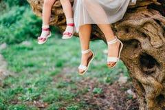 Ноги матери и ребенка Мои дочь и мать сидят дальше Стоковые Фото